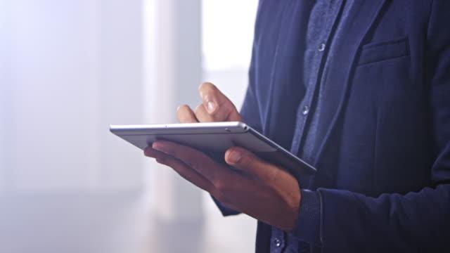 hände eines mannes, der ein digitales tablet hält und daran arbeitet - verantwortung stock-videos und b-roll-filmmaterial