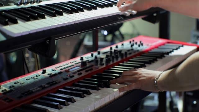 vídeos de stock, filmes e b-roll de mãos de um homem tocando um sintetizador na luz - músico pop