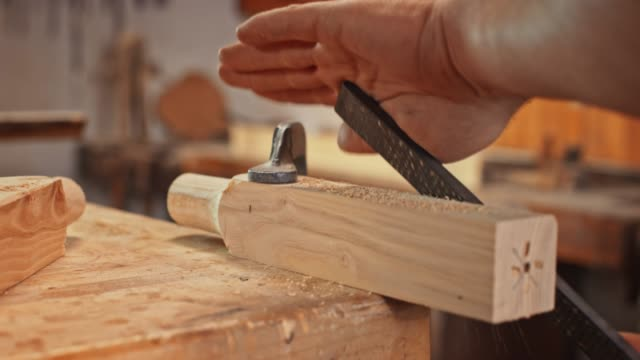 Hands of a man using a rasp to shape a piece of wood held by the bar clamp