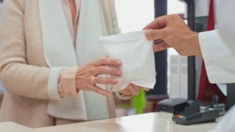 vidéos et rushes de mains d'un pharmacien plaçant le médicament d'ordonnance dans un sac blanc et le remettant au client - exactitude