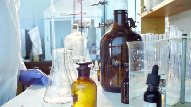 vídeos de stock, filmes e b-roll de mãos de um cientista derramando a solução em frascos - amostra científica