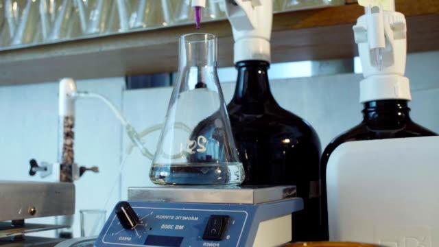 vídeos de stock, filmes e b-roll de mãos de uma solução titulada de cientista - amostra científica