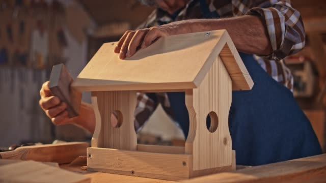 SLO MO Hands of a senior male carpenter finishing the surface of a bird house using a sanding sponge
