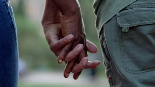 hands of a white man and a black woman intertwined. interracial love - mano donna dita unite video stock e b–roll