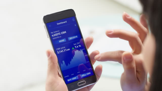 hands of a woman checking cryptocurrency statistics on her smartphone - criptovaluta video stock e b–roll