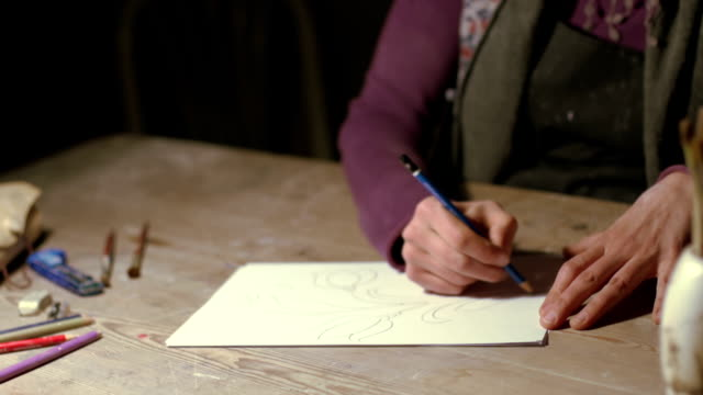 hands of a woman drawing the subject - piastrella video stock e b–roll