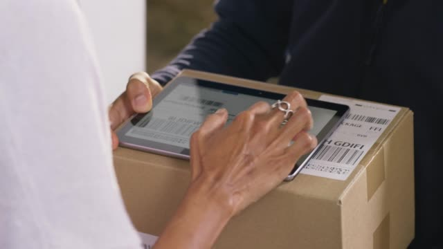 Hands of a woman opening the door and signing for the package