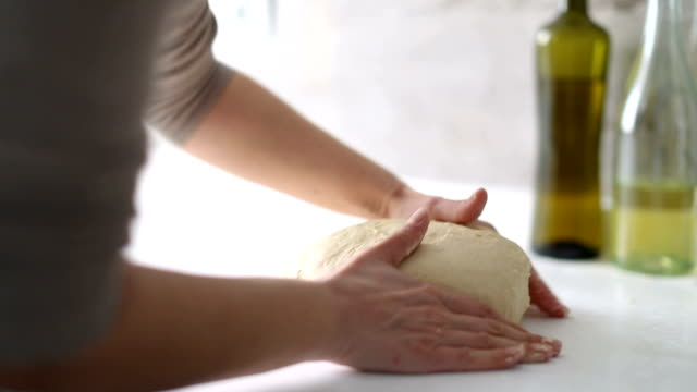 dolly: hands of a woman preparing the dough to make homemade bread or pastry - impasto video stock e b–roll