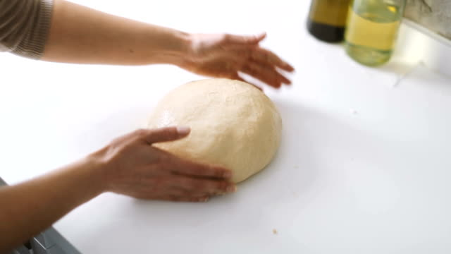 Hands of a woman preparing the dough to make homemade bread or pastry