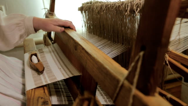 Hands of a woman weaving on an old wooden loom video