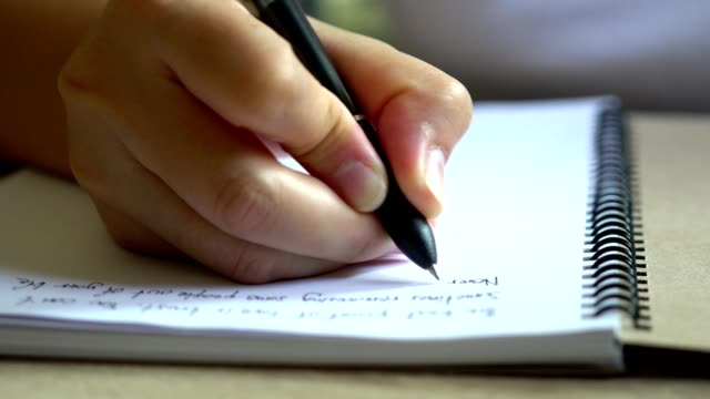 Hands of a woman writing blank notebook on table video