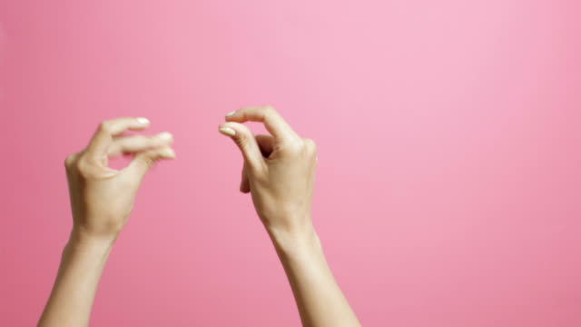 hands of a young woman snapping fingers to the beat with joy on a pink studio background hands of a young woman snapping fingers to the beat with joy on a pink studio background snapping stock videos & royalty-free footage