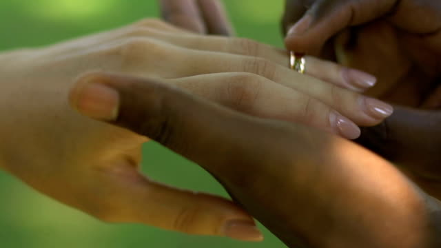 Hands of afro-american man wearing engagement ring on girlfriends finger, couple