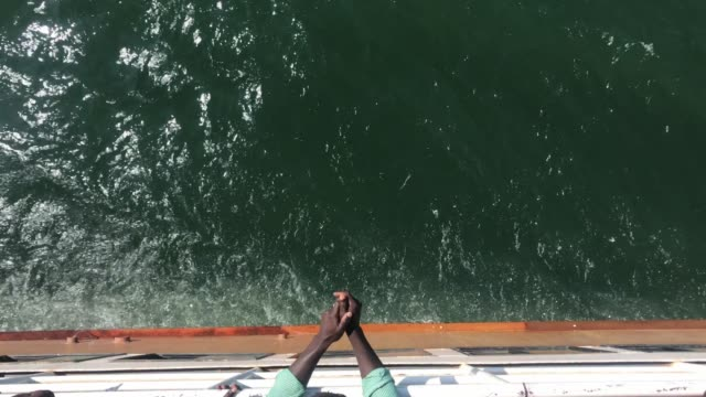 Hands of an African man lay on the side of a ship