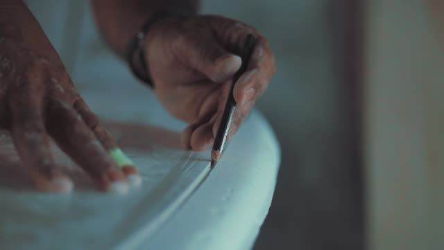 DETAIL: Hands of an experienced manual surf shaper draw a line on a blank. Home made professional surfboards. DETAIL: Hands of an experienced manual surf shaper draw a line on a blank. Home made professional surfboards. molding a shape stock videos & royalty-free footage