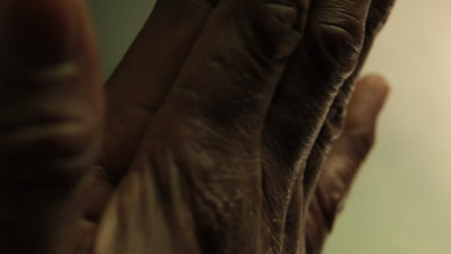 hands of an old african american man praying.  manos de un hombre viejo afro-americano, rezando - pelle video stock e b–roll