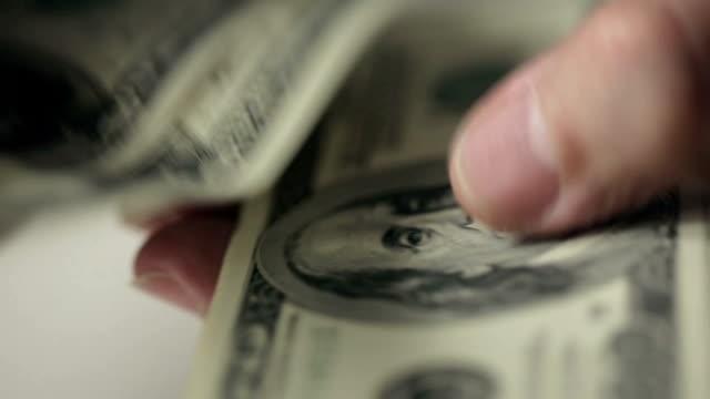 mani di un anziano uomo di conteggio banconote da cento dollari - avidità video stock e b–roll