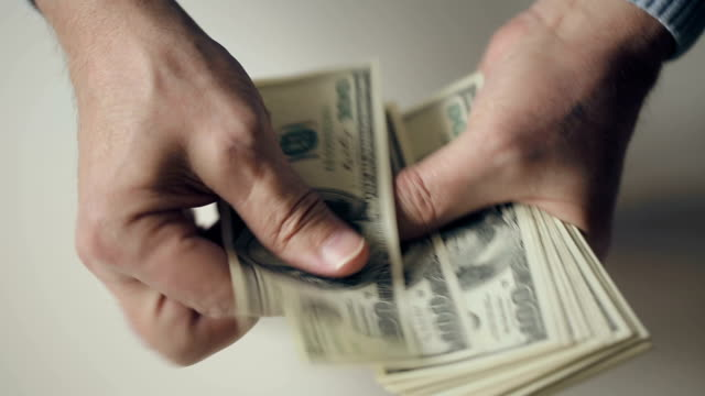 Hands of an old man counting hundred dollar bills video