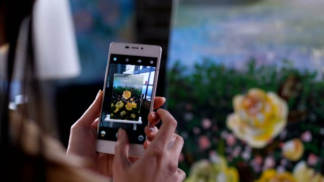 Hands of artist taking smartphone photo of canvas