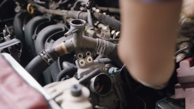 Hands of Auto Mechanic Changing and Repairing Cool Radiator Coolant in Garage.
