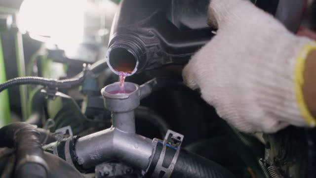 hands of auto mechanic pouring filling coolant in cool radiator in garage. - klucz ręczne narzędzie filmów i materiałów b-roll