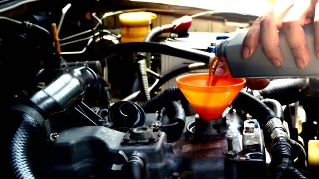 vidéos et rushes de mains du garagiste versant nouveau huile lubrifiant dans le moteur. concept de voiture de maintenance. - entonnoir