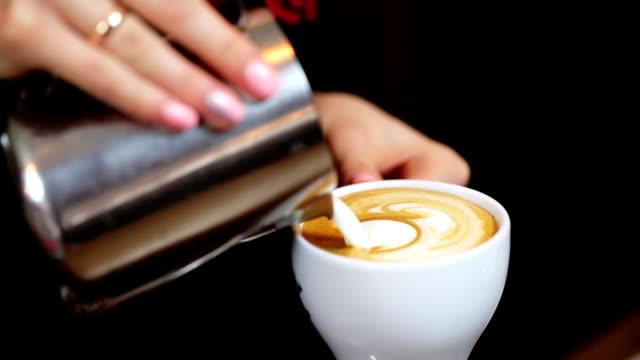 バリスタ作り手のラテやカプチーノコーヒーを注ぐミルクのラテをお楽しみください。 - ソーサー点の映像素材/bロール