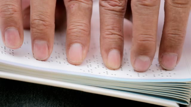 Mains d'homme aveugle lecture Braille langue sur livre - Vidéo