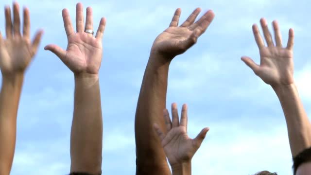 Hands of boys and men raised to volunteer video