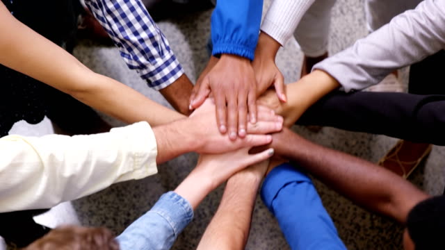 Hands of business team stacking their hands together video