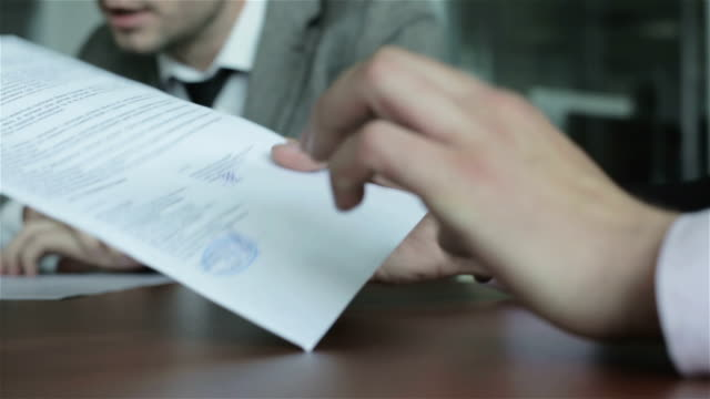 Hands of businessman are on the document. video