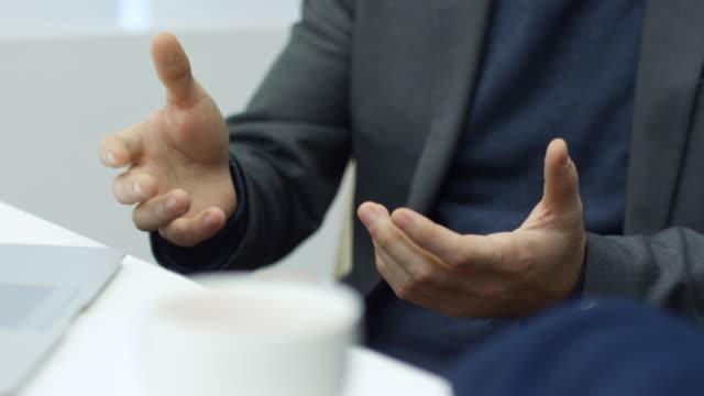 vidéos et rushes de mains d'homme d'affaires, parler d'autre chose - expliquer