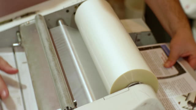 hands of caucasian man run a roll laminator during its work - литография стоковые видео и кадры b-roll