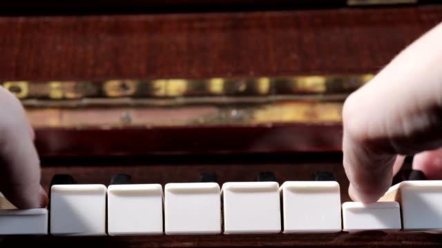 vídeos de stock e filmes b-roll de hands of caucasian woman playing piano, close up, side view - compositor