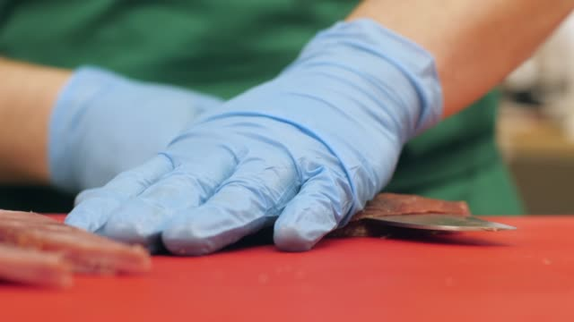 Hands of cook using knife for cutting jerky meat while cooking in restaurant Hands of cook using knife for cutting jerky meat while cooking in restaurant. Cook in kitchen cutting meat sausage close up jerky stock videos & royalty-free footage