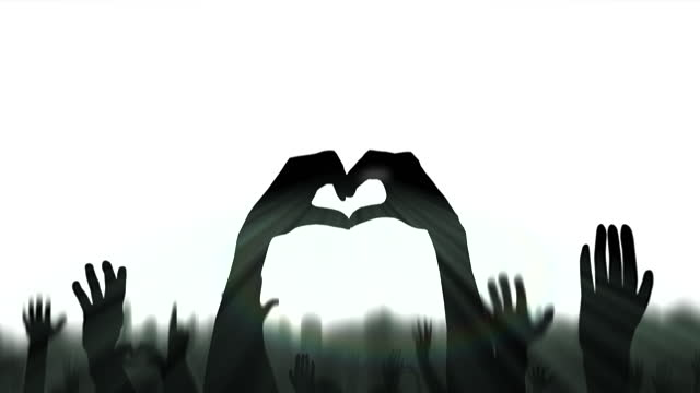 Hands of dark silhouette shapes heart in a crowd celebrating