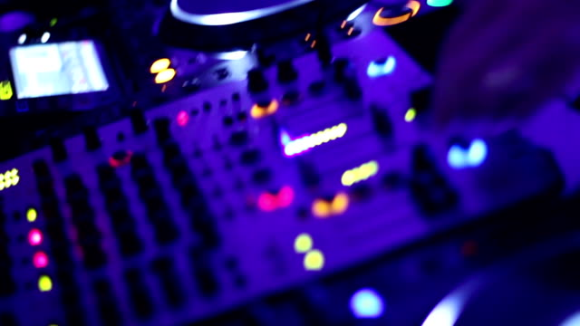 Hands of DJ tweak controls on record deck in nightclub video