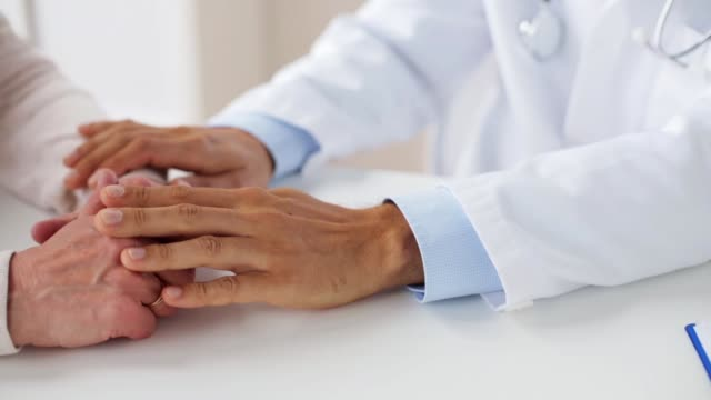 hands of doctor supporting senior woman at clinic medicine, healthcare and people concept - hands of doctor supporting senior woman at hospital general practitioner stock videos & royalty-free footage