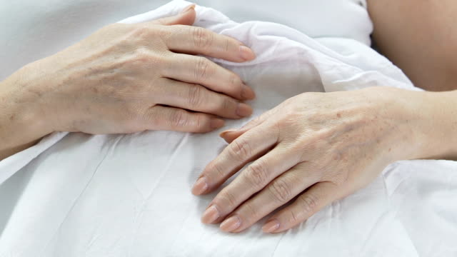 Hands of elderly woman lying in bed, wrinkled skin, aging person, experience video