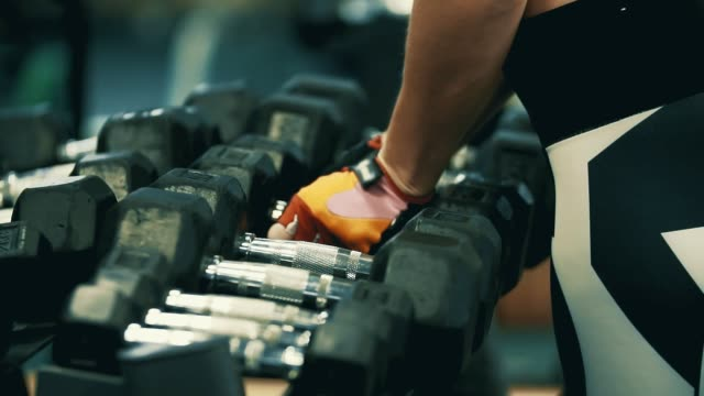 Hands of female athlete taking heavy dumbbells. Getting ready for workout video