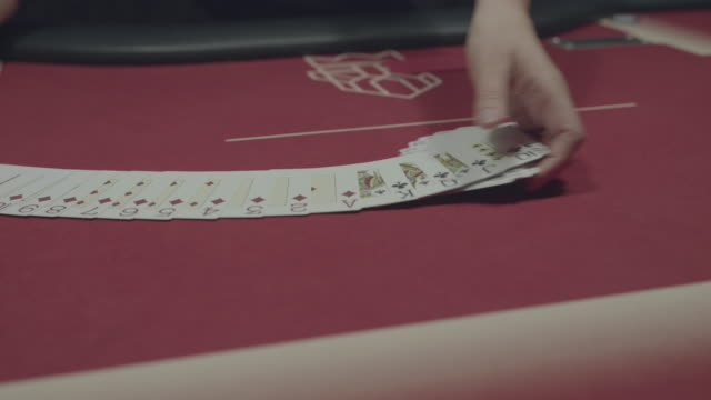 Hands of female casino dealer spreads poker cards out on table and folds them video