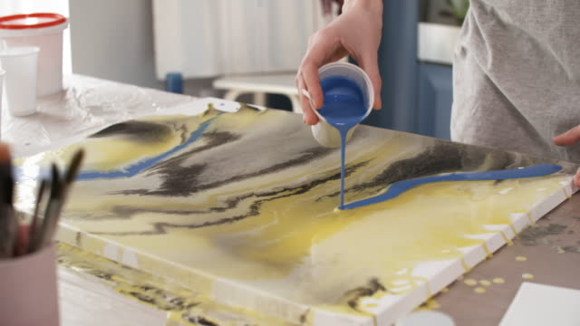 Bидео Hands of Female Painter Pouring Paint and Tilting Canvas