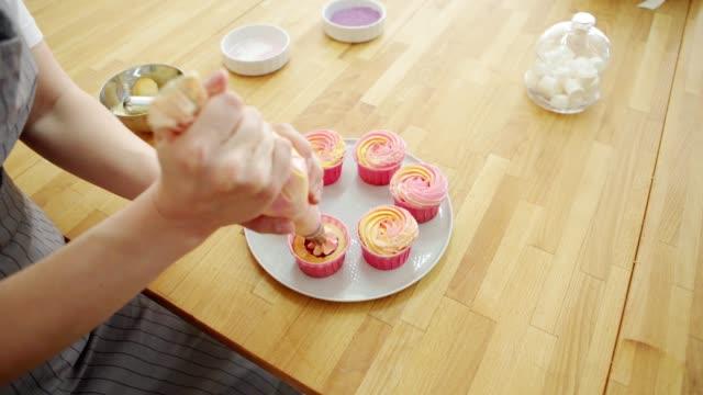 ベリーのガナッシュで満たされた手作りのカップケーキを飾るためにパイピングバッグを使用した女性のペストリーシェフの手ピンクの黄色の buttercream フロスティング、高角度のクローズア - カップケーキ点の映像素材/bロール