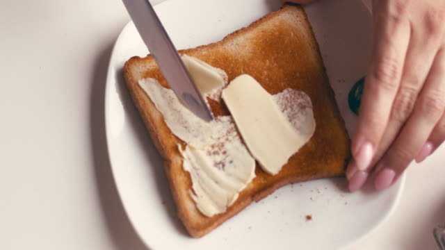 Hands of female spreading butter and jam on a slice of bread High angle of hands of female spreading butter and jam on a slice of bread bread stock videos & royalty-free footage