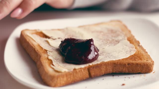 stockvideo's en b-roll-footage met handen van vrouwelijke verspreiden jam toast - geroosterd brood
