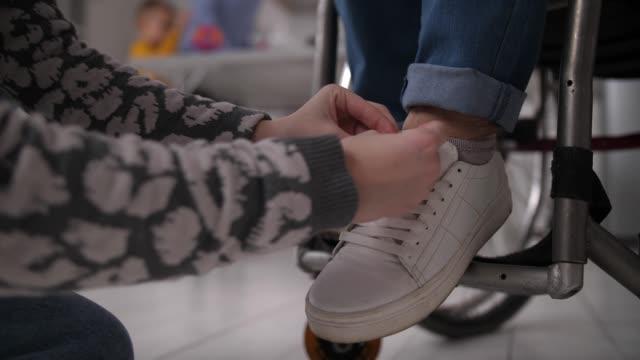 händer av flicka snörning skor för funktionshindrade mormor - fysiskt funktionshinder bildbanksvideor och videomaterial från bakom kulisserna