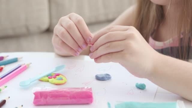 Hands of girl making shape using plasticine video