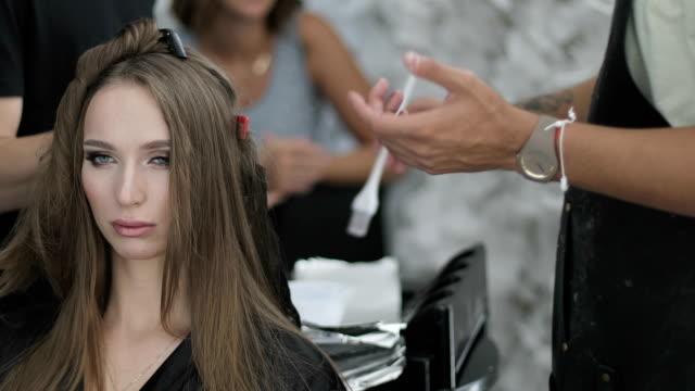 hände von friseur stylist ist farbstoff auf lange frau haar anwenden. - haartönung stock-videos und b-roll-filmmaterial
