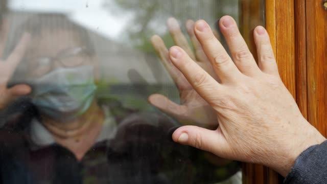 mani di speranza. un uomo e una donna anziani toccano i palmi delle mani attraverso la finestra di vetro che li separa l'uno dall'altro durante il rigoroso periodo di quarantena. - hand on glass covid video stock e b–roll