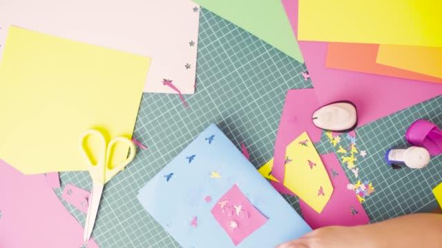 vídeos de stock e filmes b-roll de hands of little girl gluing colored paper - cortar atividade
